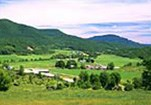 An aerial scene of farm buildings and green pastures nestled in Vermont's forested hills.