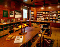 Books fill the shelves, and daylight and small lamps warm a large wooden table in the reading area of the bookstore.