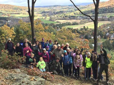 Group of hikers on top of south peak overlooking Woodstock Vermont