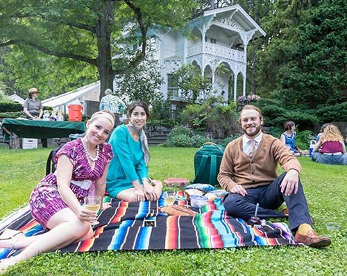 Four people sitting on a colorful blanket picnicking on the Belvedere lawn during Summer Soiree event