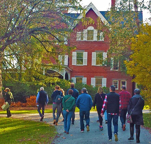 Ranger leads a group of visitors toward the Mansion in the Fall light