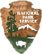 The symbol of the National Park Service, the brown chiseled arrowhead logo depicts a bison, an evergreen tree, a lake, and a snow-covered mountain peak.