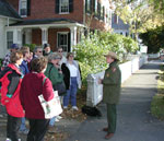 Standing next to an old brick and white clapboard house, a park ranger talks with 11 people.