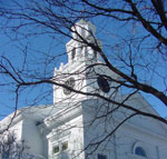 Looking from below, the steeple of this white wooden church is framed by the leafless branches of a nearby tree.