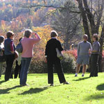 A ranger speaks with a group of people on a sloping green lawn, lit by the waning afternoon light of a fall day.