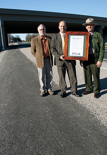 Park City Mayor David Lyons and Mammoth Cave NP Acting Superintendent Bruce Powell present a proclamation of appreciation to Greg Merideth of KYTC along the new section of bike trail that connects Park City to the national park.