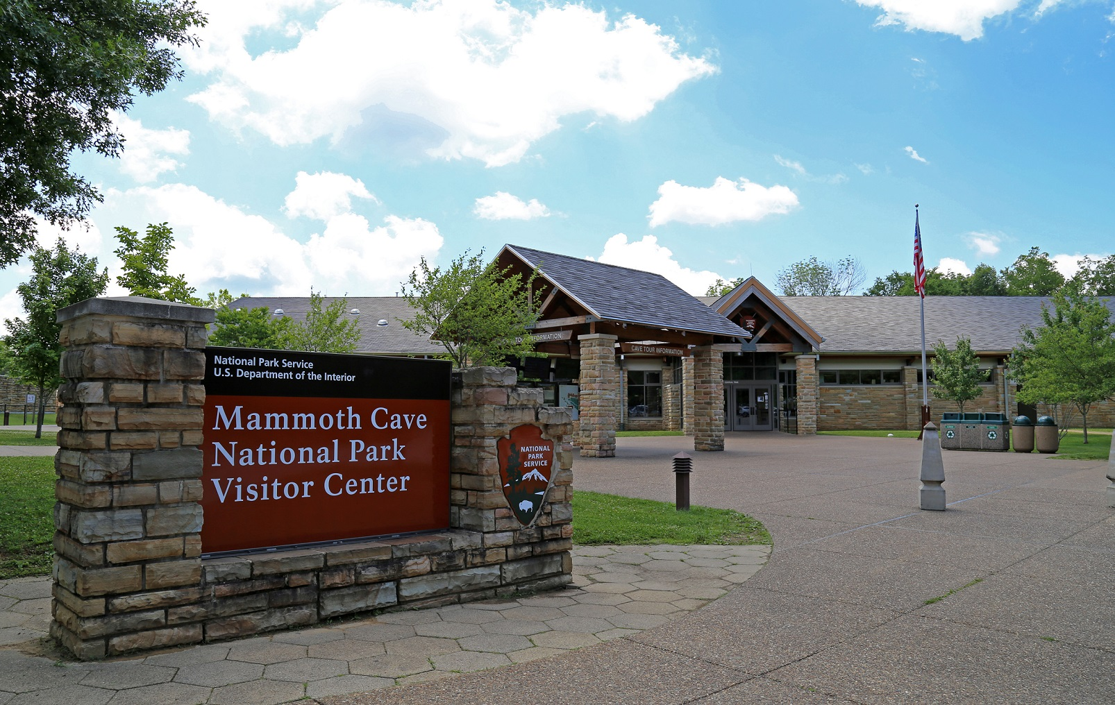 Image of large Mammoth Cave National Park Visitor Center sign with building and flagpole in the background.