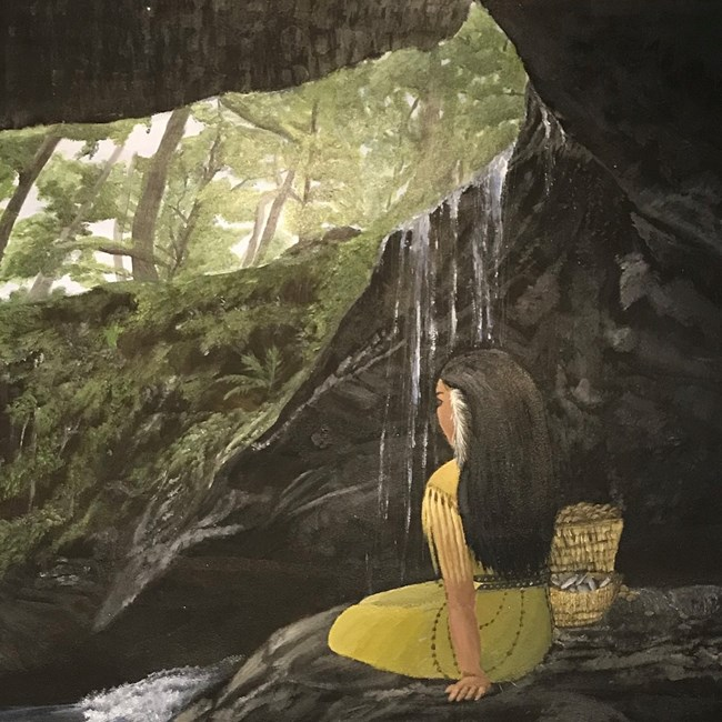 A woman sits in a dark cave with water flowing over the mouth of the cave while a green forest is visible in the cave opening above.