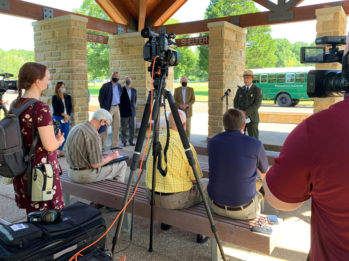 Several reporters with video cameras film a ranger wearing the NPS uniform and flat hat as he speaks into a microphone at an outdoor news event.