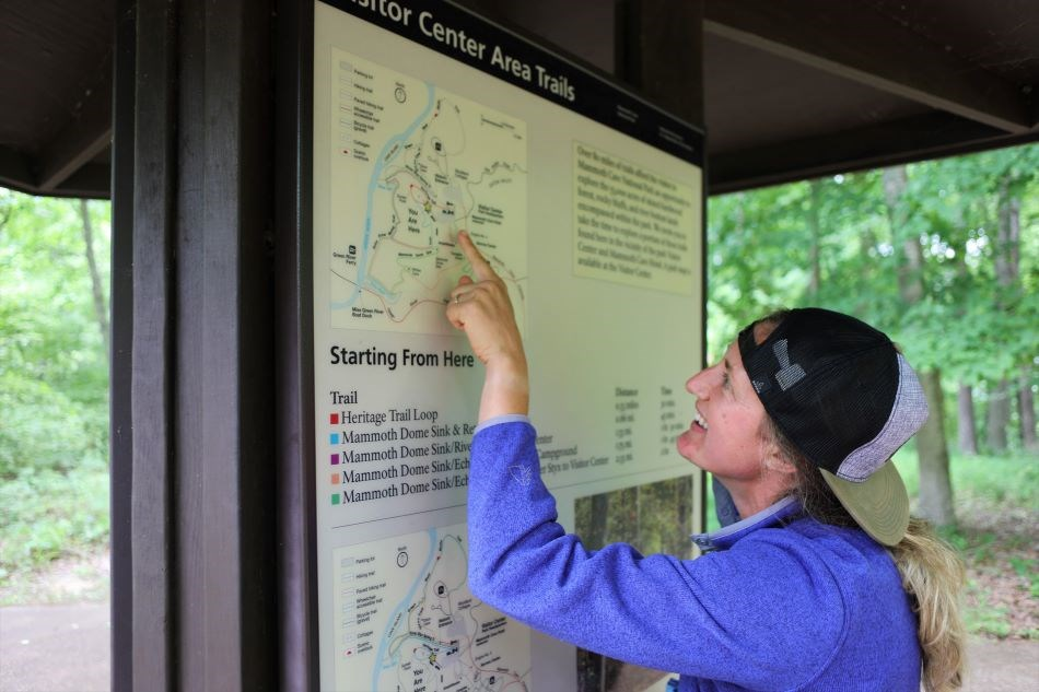 A visitor points out her route using a large kiosk map.