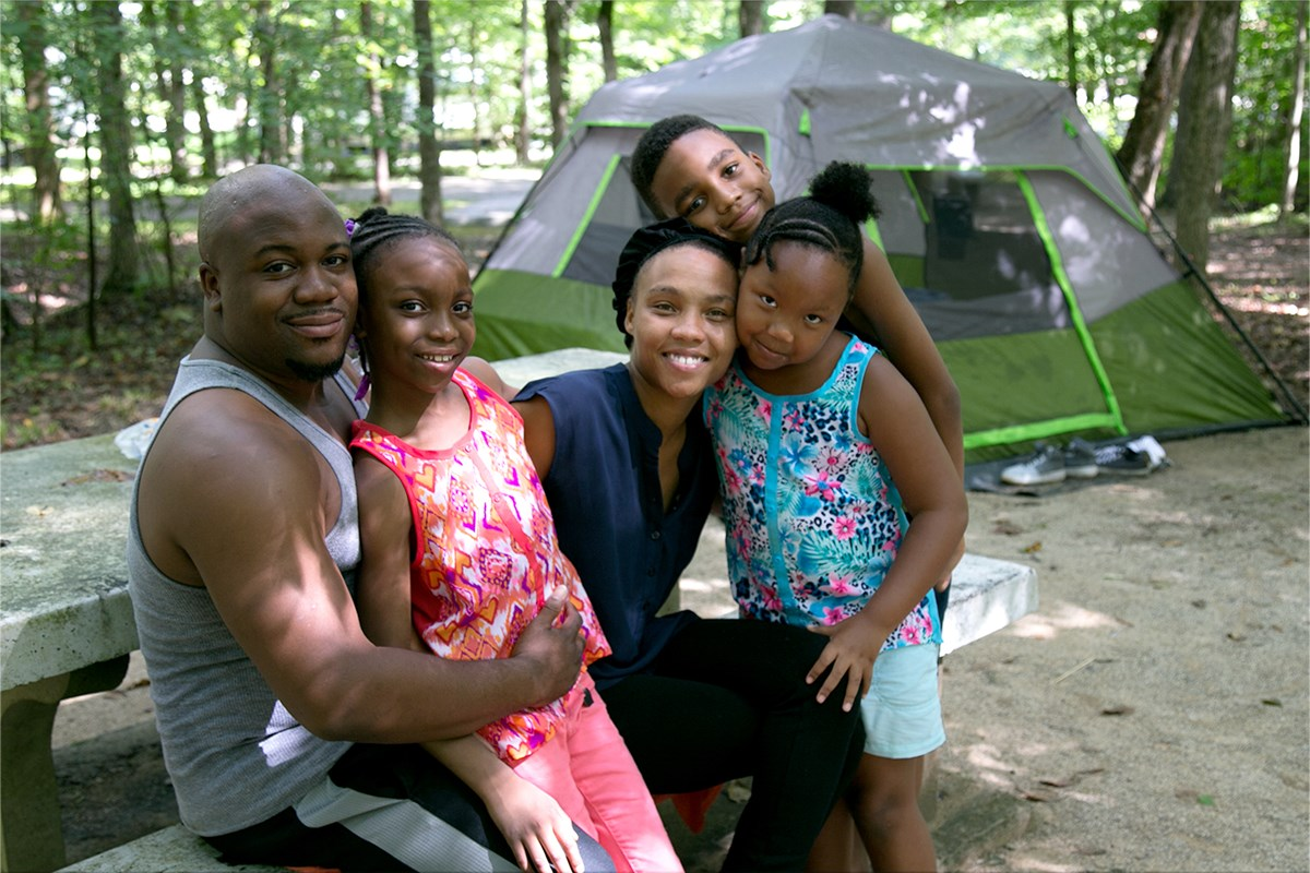 A family, with a father, mother, two young daughters and a young son near their tent. All are smiling and looking toward the viewer.