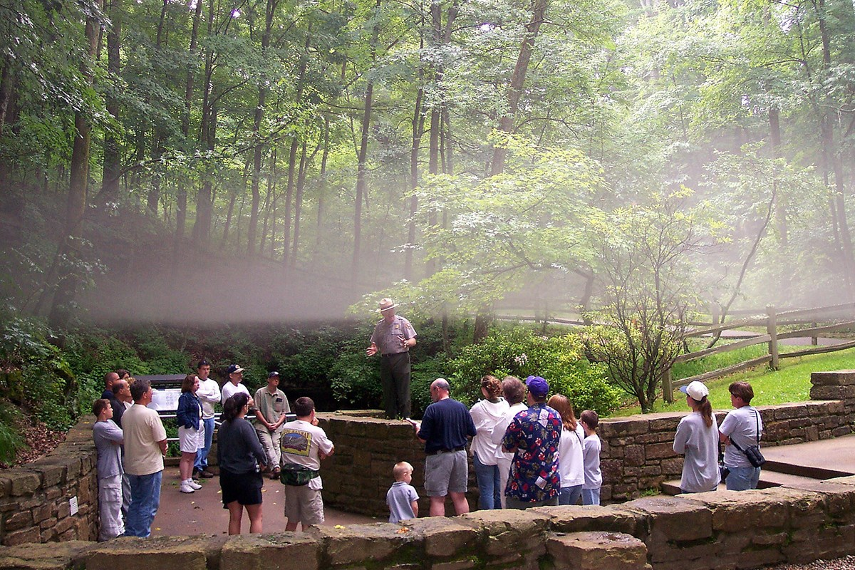Fog hangs over a ranger giving a talk to a group of visitors at the cave's Historic Entrance.