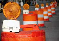 Line of orange traffic barrels with warning flashers on the top.