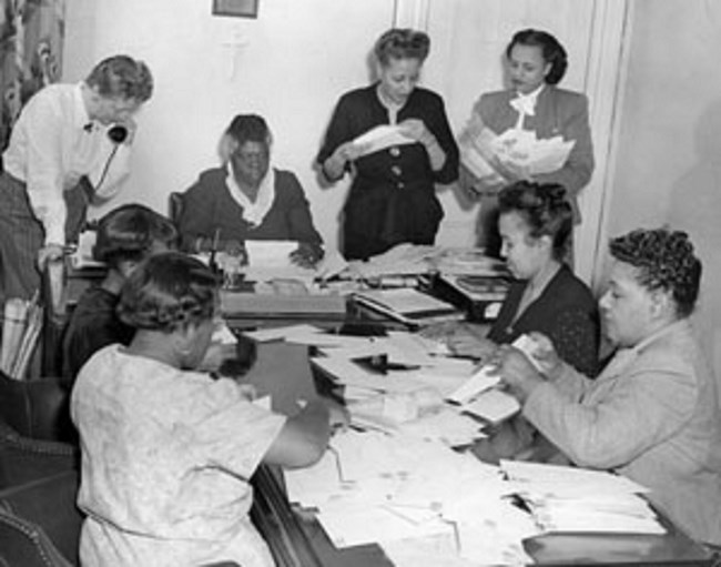 Bethune and her council members sitting at a desk going through paper work