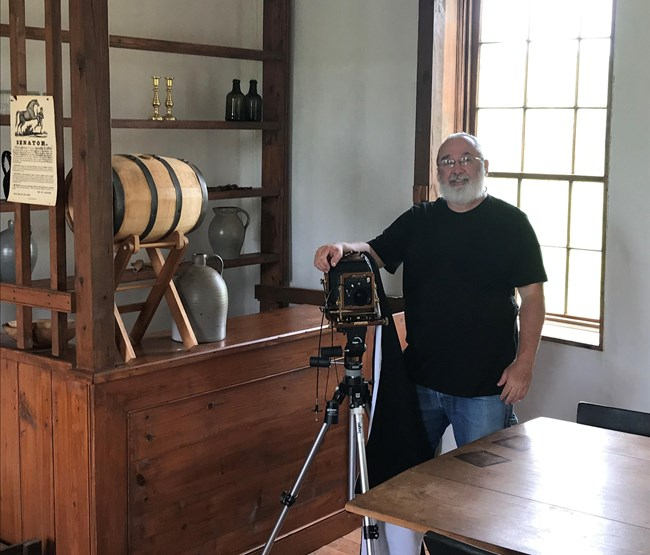 "Artist-In-Residence poses with his old-time camera in the ""tavern"" room of the Stone House."