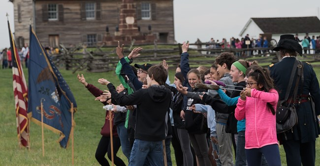 A group of children practice firing after marching in column while a living historian directs them to fire.