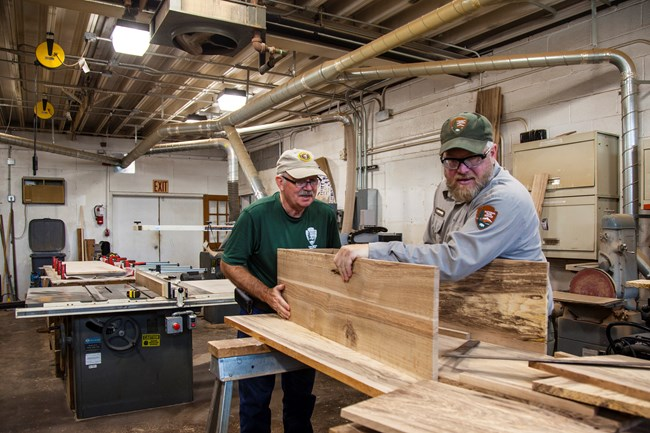 An NPS employee and a volunteer fit a piece of wood onto a coffin
