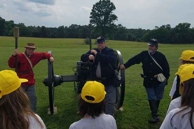 Three volunteers in living history uniforms flank a cannon while students ask questions in front of them.