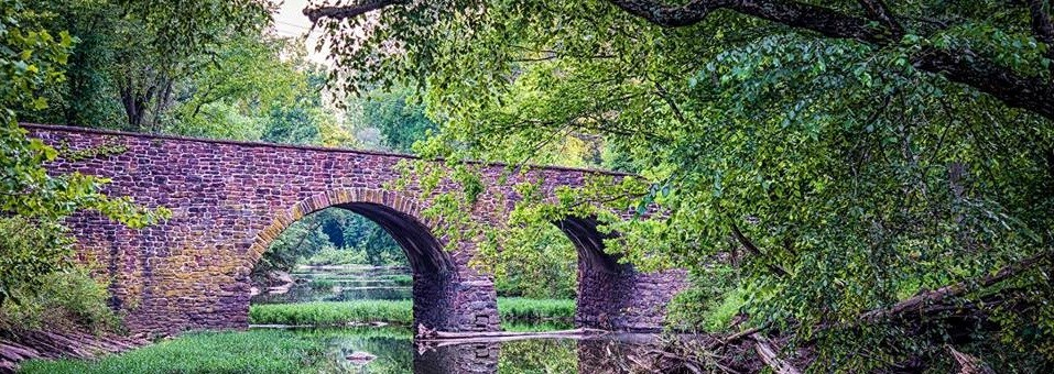 Historic Stone Bridge over a body of water during summer