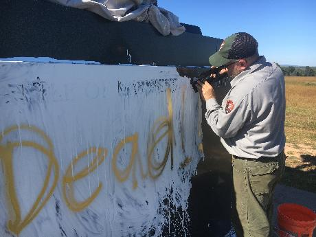 A National Park Service preservation expert works to clean white paint from the granite base of the Stonewall Jackson Monument at Manassas National Battlefield Park.