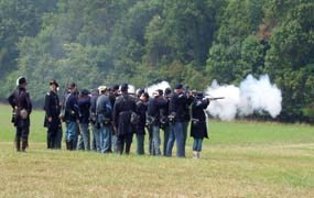 Historical re-enactors firing their muskets during military drill