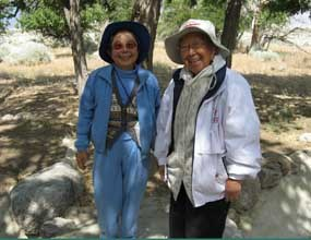 Two smiling women stand in the remnants of the Block 22 garden.
