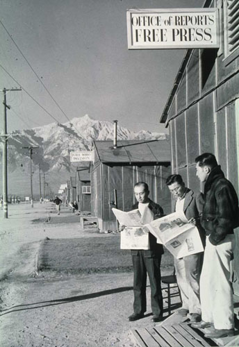Group reading newspaper in front of office