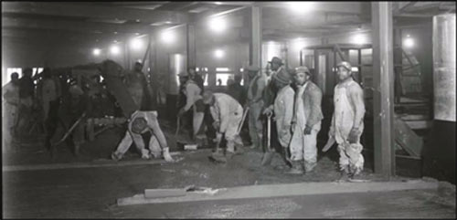 African-American workers laying concrete foundation