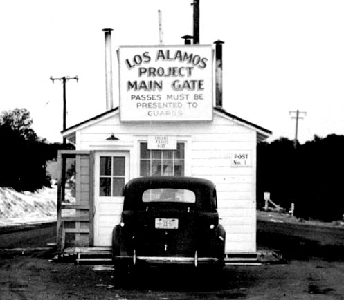 black and white image with car parked at a small building