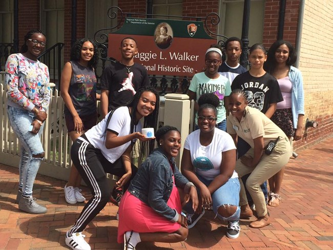 Student participants in the Summer Youth Leadership Institute pose with an intern in front of the Maggie L. Walker National Historic Site sign