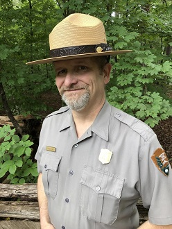 Park ranger in uniform standing in front of trees