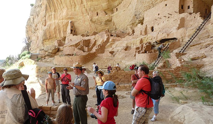 Interpretive ranger with visitors at the Long House cliff dwelling.