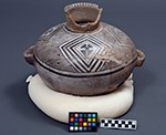 Large, white pottery jar with painted black geometric designs and handles on each side.