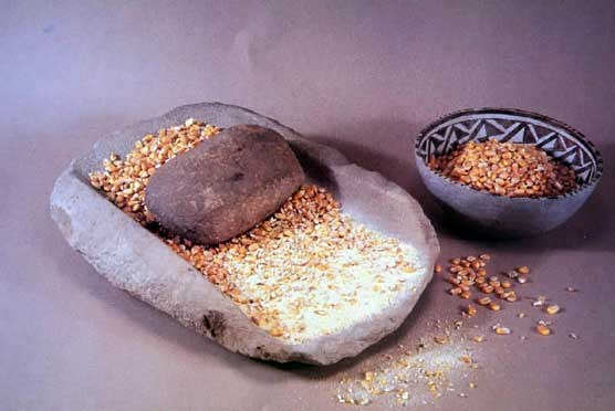 Corn filled mano and metate with bowl of corn alongside