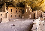 Kiva courtyard showing kiva roof, kiva entrance, and ladder with pueblo rooms in background