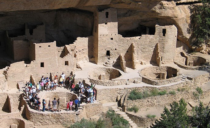 Tour group encircling Kiva F at Cliff Palace