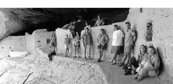 Thirteen archeologists posing in front of cliff dwelling at Gila Cliff Dwellings NM.