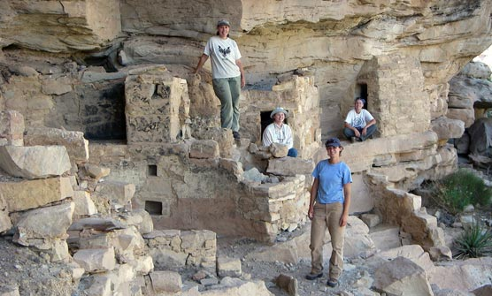 Fort Lewis College intern with archeologists in cliff dwelling.