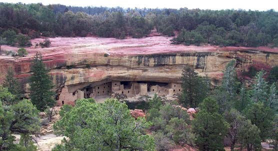 View of Spruce Tree House cliff dwelling with red slurry on mesa top above site.