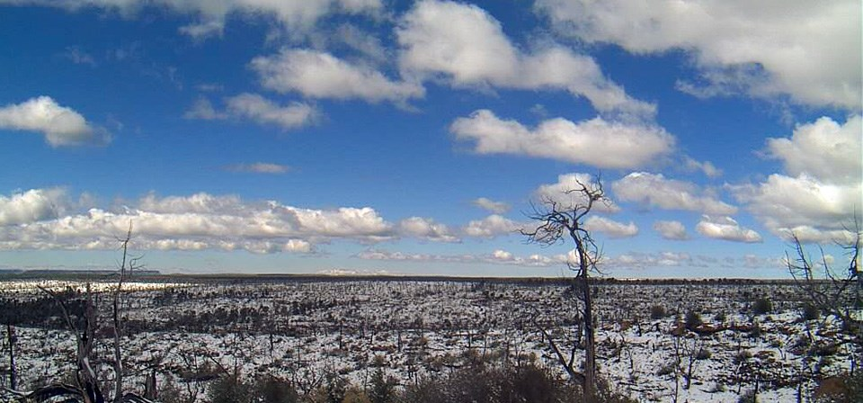 View of snowy mesa with clouded blue sky above.