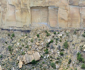 Sandstone cliff face with a square chunk of rock that has fallen away into the canyon below.