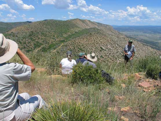 Ranger with small group in Mesa Verde's Wilderness discussing the area.
