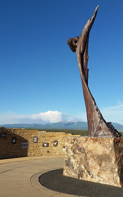 Sculpture of climber in welcome plaza with smoke billowing up from the La Plata Mountains in background.