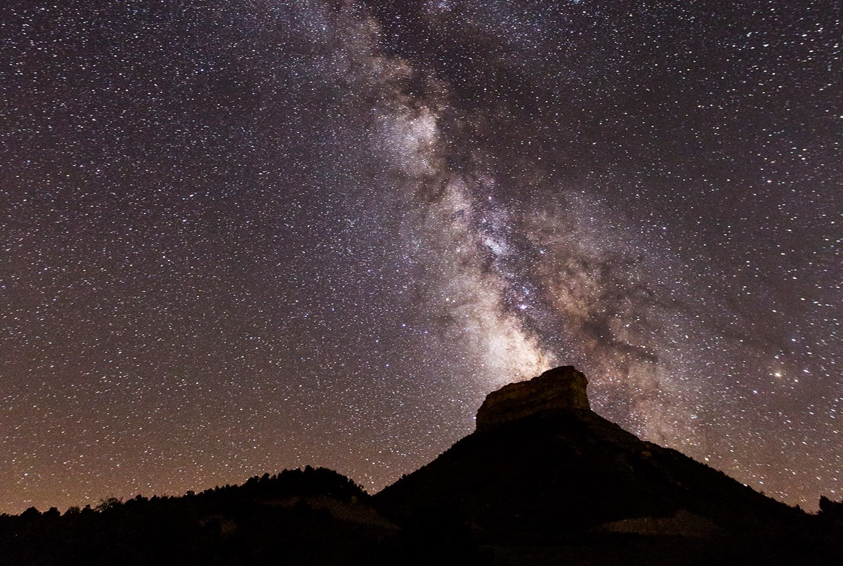 A starry sky bisected by the Milky Way rises over forested hills and the prominent mesa of Point Lookout