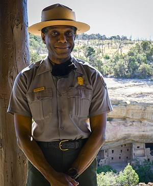 Smiling ranger in flat hat in front of an ancient, stone-masonry village.
