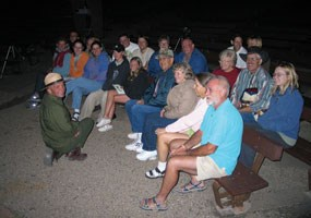 Ranger presenting an evening program to visitors in campground amphitheater.