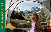 2014 Interagency Volunteer Pass. Child looking out of tent at mountain scene.