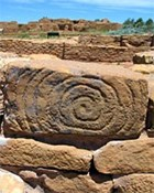 Spiral carved into a sandstone block in foreground with large, stone-masonry rooms in the background.