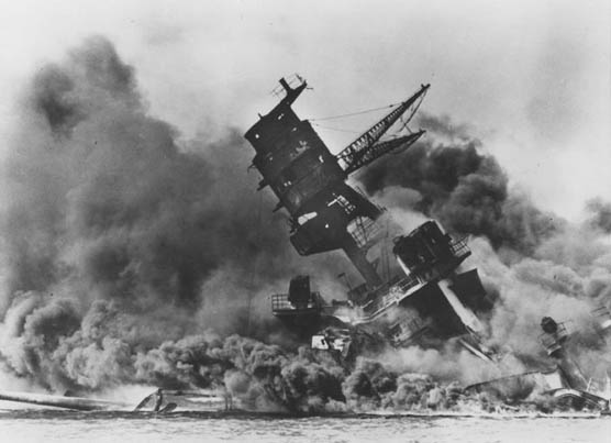 The forward superstructure and Number Two gun turret of the sunken USS Arizona afire after the attack.
