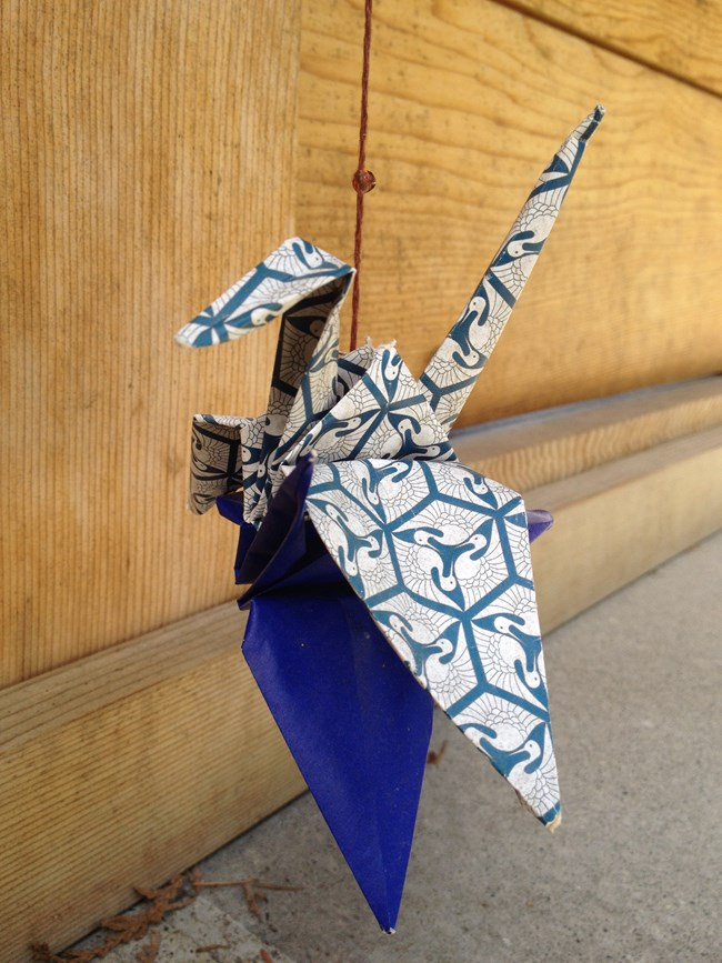 Origami crane made of blue, gray and white paper